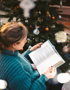 woman reading a book by a Christmas tree