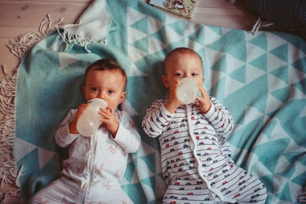 two babies drinking bottles - what should babies wear